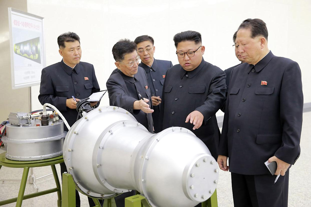 This undated picture released by North Korea's official Korean Central News Agency in September shows Kim Jong Un, center, at an undisclosed location looking at a metal casing with two bulges. (Photo: STR/AFP/Getty Images)