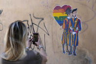 A murales showing a Swiss guard kissing a colleague, by street artist Laika, is seen on the day of the annual Pride march, in Rome, Saturday, June 26, 2021. This year's march comes amid widespread concern in Europe about legislation in Hungary that will ban showing content about LGBT issues to children and a controversial Vatican communication to Italy, criticizing a law that would extend additional protections from discrimination to the LGBT community.. (AP Photo/Gregorio Borgia)