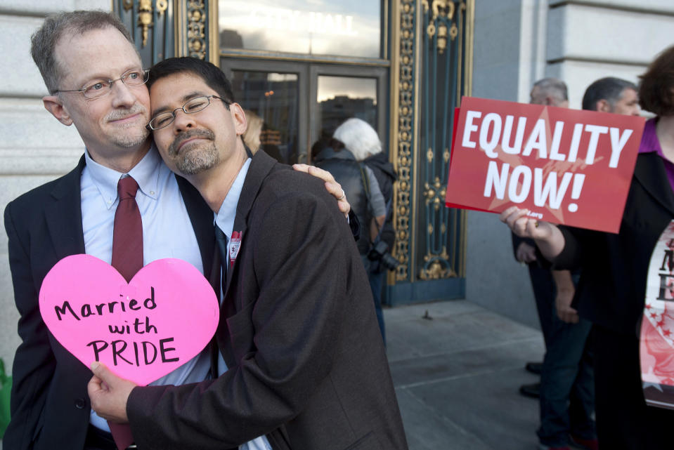 John Lewis, left, and Stuart Gaffney embrace outside San Francisco's City Hall shortly before the U.S. Supreme Court ruling cleared the way for same-sex marriage in California on Wednesday, June 26, 2013. (AP Photo/Noah Berger)