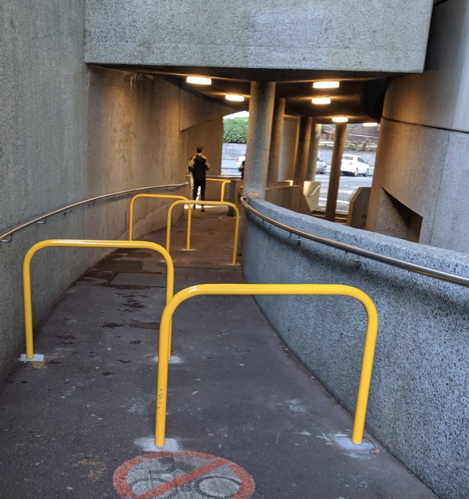 The pathway near Hamer Hall can be seen with as many as five yellow metal barriers impeding the path.