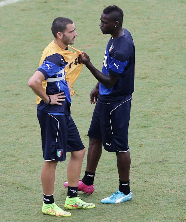 Italy's Mario Balotelli, right, holds a part of Leonardo Bonucci's practice vest as they stand on the pitch during a training session, a the day before their group D World Cup soccer match, at the Arena das Dunas in Natal, Brazil, Monday, June 23, 2014. (AP Photo/Antonio Clanni)