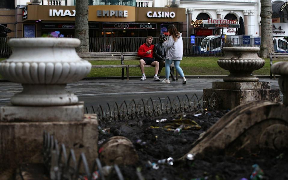 Tourists post for photos with a statue in view of rubbish left by football fans in Leicester Square on June 19, 2021 in London, England. - GETTY IMAGES