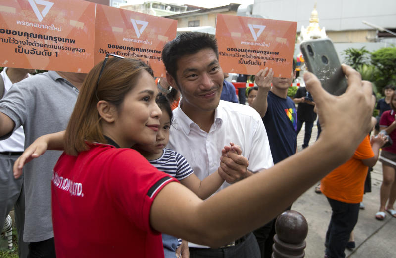A supporter takes selfies with the leader of the Future Forward Party, Thanathorn Juangroongruangkit, in Bangkok, Thailand, Wednesday, April 3, 2019. Thailand's ruling junta has filed a complaint accusing Thanathorn of sedition and aiding criminals. The Future Forward Party ran a strong third in the elections last month that were also contested by a pro-military party. (AP Photo/Sakchai Lalit)