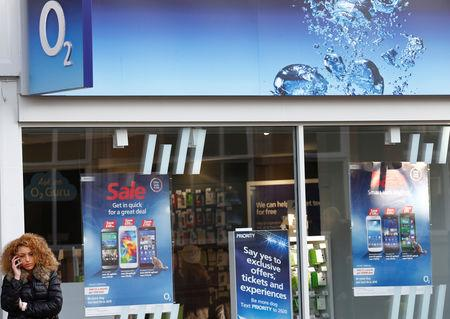 FILE PHOTO: A woman speaks on her mobile telephone outside an O2 shop in Loughborough, England