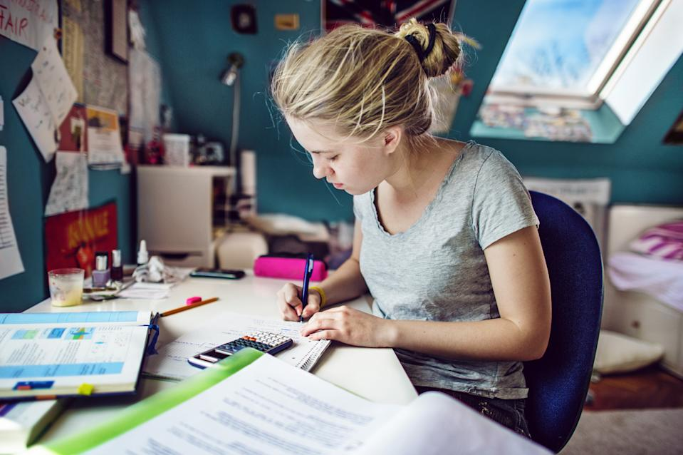 Young woman with blonde hair, sitting at a desk in her room and doing maths-homeworks
