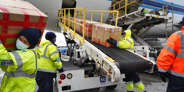 Wearing protective masks ground crew at the Los Angeles International airport unload supplies of medical personal protective equipment, PPE, from a China Southern Cargo plane upon it's arrival on Friday, April 10, 2020.