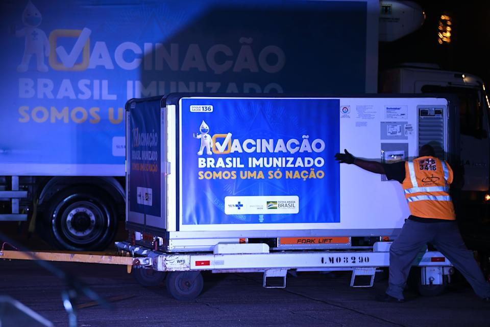 Containers carrying doses of the Oxford/AstraZeneca vaccine with a banner reading Vaccination. Brazil immunized. We are an only nation are unloaded from a cargo plane that arrived from Sao Paulo at the Galeao airport, in Rio de Janeiro, Brazil, on January 22, 2021. - Brazil received Friday a first lot with two million doses of the Oxford/AstraZeneca vaccine developed by the Serum Institute of India. (Photo by MAURO PIMENTEL / AFP) (Photo by MAURO PIMENTEL/AFP via Getty Images)