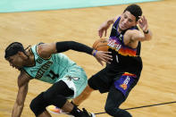 Charlotte Hornets guard Devonte' Graham, left, fouls Phoenix Suns guard Devin Booker during overtime in an NBA basketball game on Sunday, March 28, 2021, in Charlotte, N.C. (AP Photo/Chris Carlson)