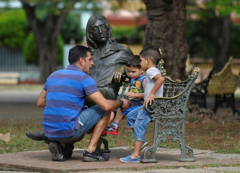 A man with his sons sit next to a statue of John Lennon in a park in Havana, on March 11, 2017
