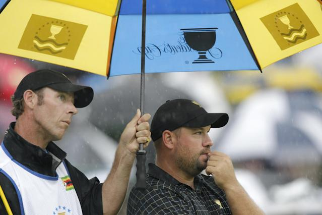 International team player Brendon de Jonge, right, of Zimbabwe, and caddie Phil Lowe wait on the sixth green during the single matches at the Presidents Cup golf tournament at Muirfield Village Golf Club Sunday, Oct. 6, 2013, in Dublin, Ohio. (AP Photo/Jay LaPrete)