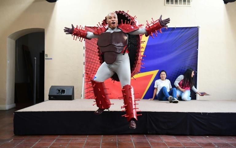Artry, who plays the Covid-19 virus, jumps off stage during rehearsals of a superhero-themed Covid-19 play at the El Sol Neighborhood Educational Center