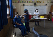 FILE - In this Monday, Feb. 15, 2021, file photo, a teacher receives a shot of the CoronaVac vaccine for COVID-19, by China's Sinovac Biotech, at Salvador Sanfuentes public school during the start of the vaccinations for educators in Santiago, Chile. It wasn't until Sinovac swooped in with 4 million doses in late January that Chile began inoculating its population of 19 million with impressive speed. (AP Photo/Esteban Felix)