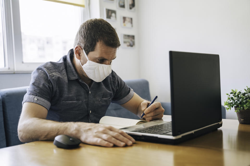 Businessman working on laptop from home wearing protective mask. COVID- 19. Coronavirus epidemic.