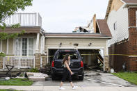 <p>A resident of a neighbourhood hit by a tornado walks past a home that has had its second floor blown off, in Barrie, Ont., on Thursday, July 15, 2021. THE CANADIAN PRESS/Christopher Katsarov</p>