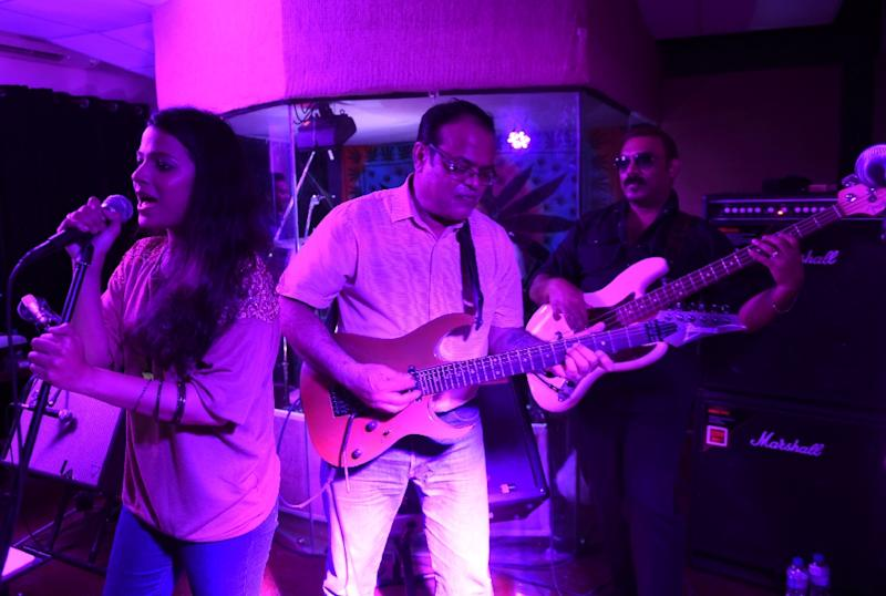 Musician Alycia Dias (L) sings as her father Max Dias (C) plays the guitar as they perform at a private bar in Karachi (AFP Photo/Asif Hassan)