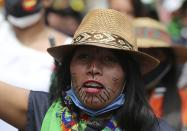 An Indigenous woman marches during a national strike in Bogota, Colombia, Wednesday, Oct. 21, 2020. Workers' unions, university students, human rights defenders, and Indigenous communities held a day of protest in conjunction with a national strike across Colombia to protest against the assassinations of social leaders, in defense of the right to protest and to demand advances in health, income and employment. (AP Photo/Fernando Vergara)