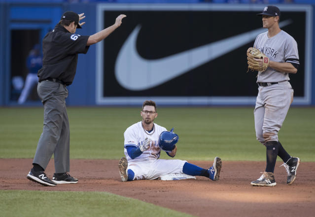 Toronto Blue Jays' Eric Sogard sits on the bag after hitting a double, next to New York Yankees' DJ LeMahieu during the first inning of a baseball game Thursday, June 6, 2019, in Toronto. (Fred Thornhill/The Canadian Press via AP)