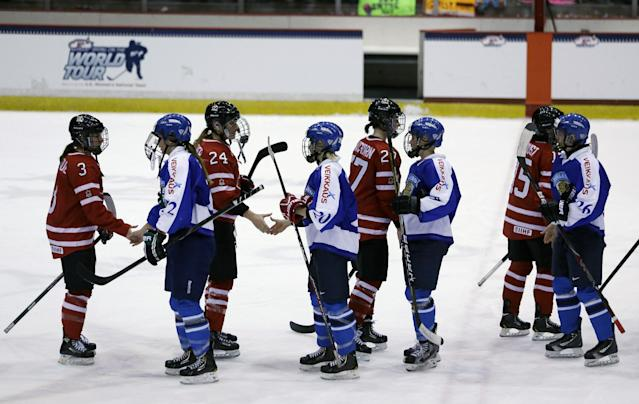 Players from Finland (wearing blue) and Canada shake hands after Canada's 6-3 win in the Four Nations Cup women's championship hockey game on Saturday, Nov. 9, 2013, in Lake Placid, N.Y. (AP Photo/Mike Groll)