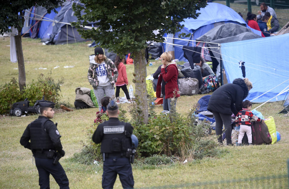 French police officers watch migrants packing their belongings in a camp of Grande Synthe, northern France, Tuesday, Sept.17, 2019. French police are evacuating at least 900 migrants from a gym near the English Channel, citing concerns about security and hygiene. (AP Photo)