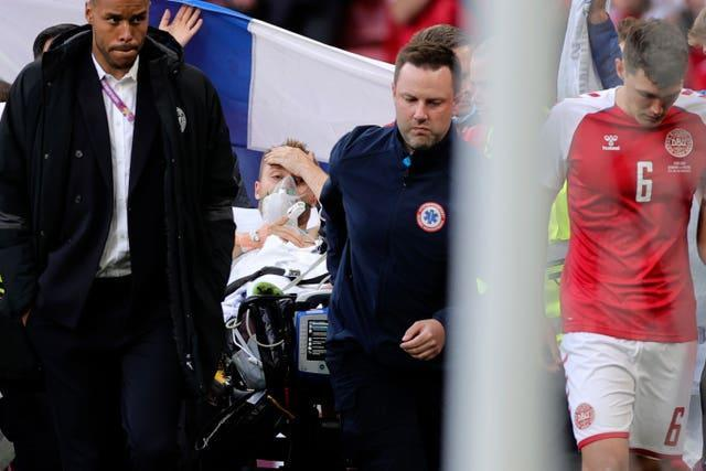 Paramedics using a stretcher to take Denmark's Christian Eriksen off the pitch after he collapsed