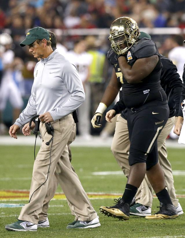 Baylor's Andrew Billings, right, leaves the field holding his right shoulder as coach Art Briles, left, walks off with him during the first half of the Fiesta Bowl NCAA college football game against Central Florida on Wednesday, Jan. 1, 2014, in Glendale, Ariz. (AP Photo/Ross D. Franklin)