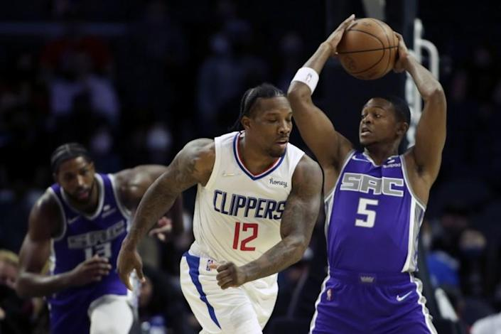 Sacramento Kings guard De'Aaron Fox (5) pulls back the ball as Los Angeles Clippers guard Eric Bledsoe (12) takes a swipe at the ball during the first half of a preseason NBA basketball game Wednesday, Oct. 6, 2021, in Los Angeles. (AP Photo/Alex Gallardo)