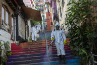 Thiago Firmino, right, sprays disinfectant to help contain the spread of the new coronavirus, in the Santa Marta slum of Rio de Janeiro, Brazil, Saturday, April 24, 2021. (AP Photo/Bruna Prado)
