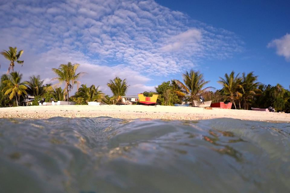 Palm trees and sand are see from the lagoon back to the shore in Funafuti, Tuvalu. Source: AAP