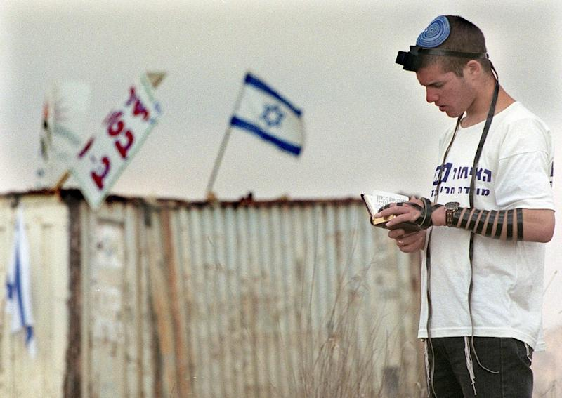 """A Jewish settler from """"The Generation of the Future"""" movement prays at the Shvut Rachel settlement in an attempt to prevent the Israeli Army from dismantling it (AFP Photo/Menahem Kahana)"""