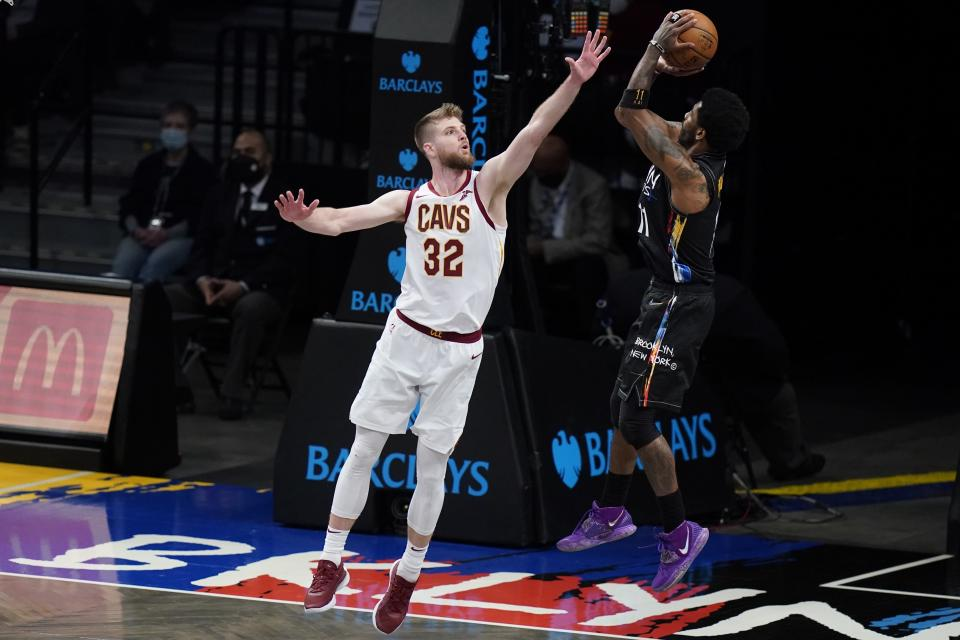 Cleveland Cavaliers' Dean Wade, left, defends Brooklyn Nets' Kyrie Irving, right, during the second half of an NBA basketball game Sunday, May 16, 2021, in New York. (AP Photo/Frank Franklin II)