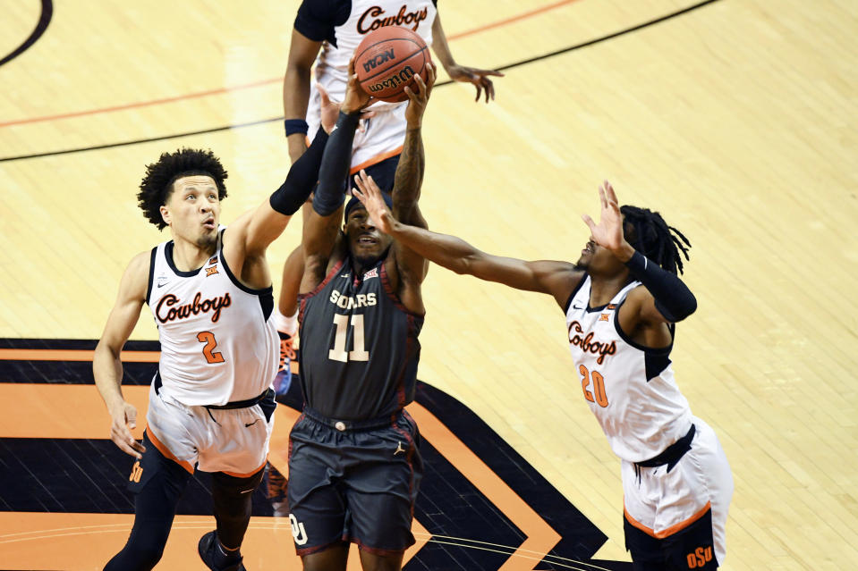 Oklahoma State guards Cade Cunningham (2) and Keylan Boone (20) attempt to block a shot by Oklahoma guard De'Vion Harmon (11) during an NCAA college basketball game Monday, March 1, 2021, in Stillwater, Okla. (AP Photo/Brody Schmidt)