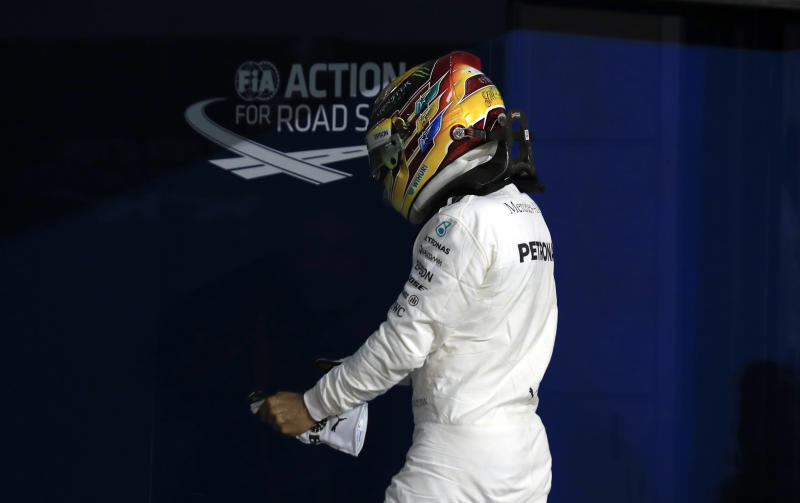 Mercedes driver Lewis Hamilton of Britain takes his gloves off after he clocked the second fastest time during the qualifying session for the Bahrain Formula One Grand Prix, at the Formula One Bahrain International Circuit in Sakhir, Bahrain, Saturday, April 15, 2017. The Bahrain Formula One Grand Prix will take place on Sunday. (AP Photo/Hassan Ammar)