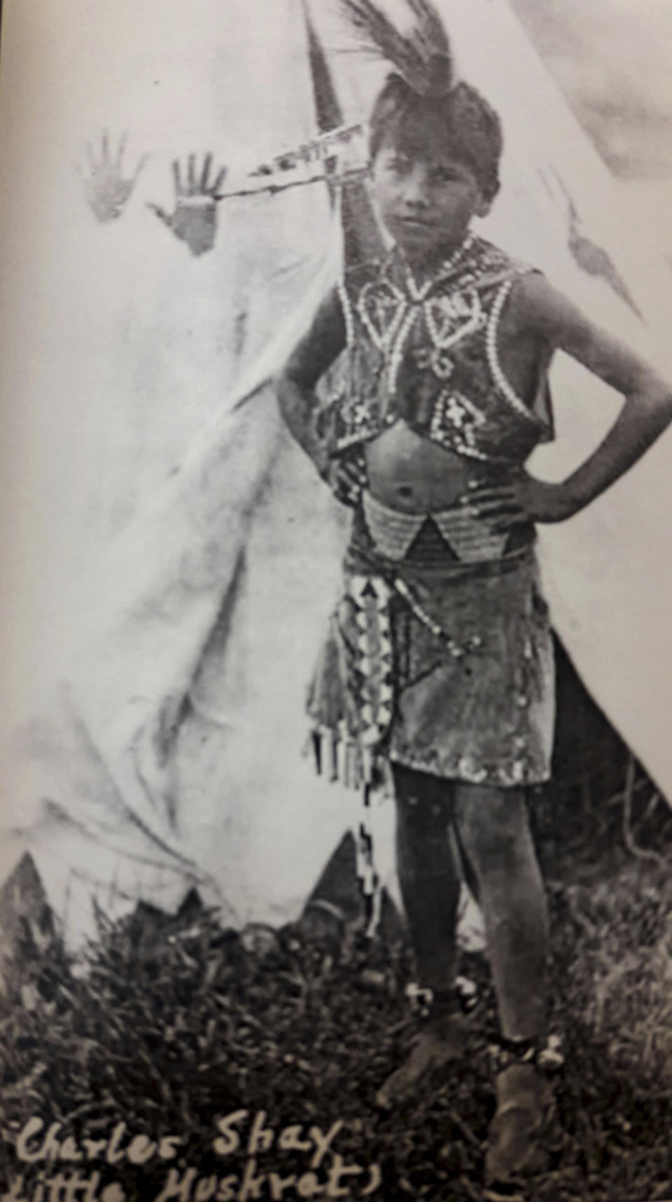 In this undated image provided by the Charles Shay Family Archive, Charles Norman Shay poses in native dress as a young boy in Indian Island, Maine. Shay, a D-Day veteran, was a medic who on June 6, 1944, landed on Omaha Beach, where he helped drag wounded soldiers out of the rising tide. (Charles Shay Family Archive via AP)