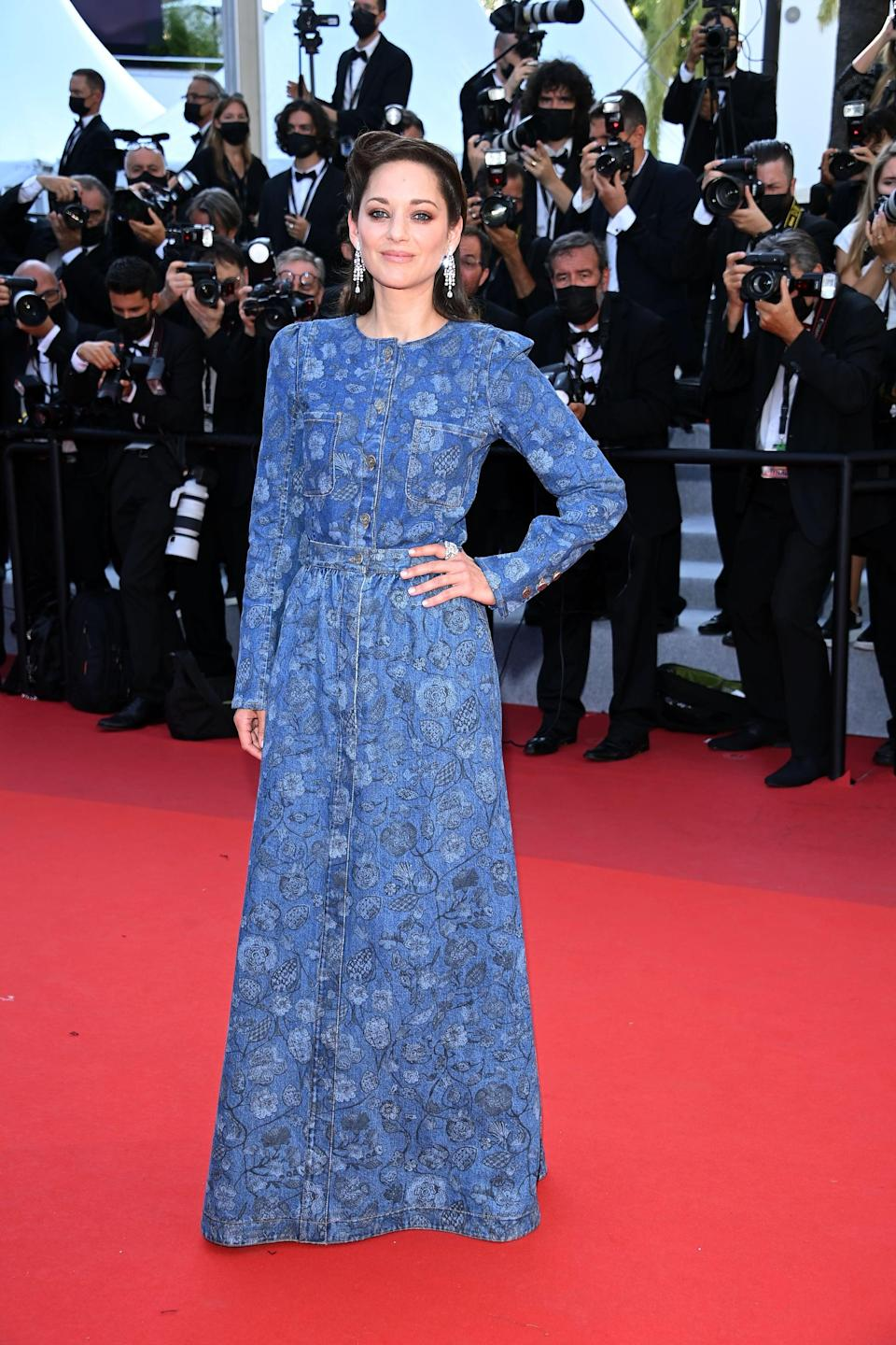 <p>Wearing a blue floral Chanel dress.</p>