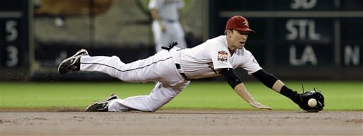 Houston Astros shortstop Jed Lowrie dives for a hit by Philadelphia Phillies' Jimmy Rollins during the first inning of a baseball game on Saturday, Sept. 15, 2012, in Houston. Rollins was safe at first with a single. (AP Photo/David J. Phillip)