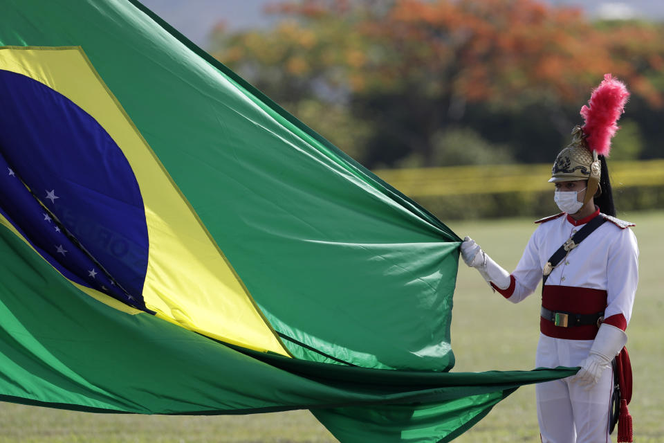 A soldier from the Presidential Guard Battalion takes part in a national flag-raising ceremony outside the presidential official residence, Alvorada Palace, in Brasilia, Brazil, Tuesday, Oct. 27, 2020, amid the COVID-19 pandemic. (AP Photo/Eraldo Peres)