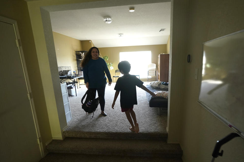 Heather Buen, left, picks up a school bag and reminds her son Cody to do his homework Monday, Oct. 4, 2021, in Fort Worth, Texas. A year and a half in, the pandemic is still agonizing families. There is still the exhaustion of worrying about exposure to COVID-19 itself, and the policies at schools and day cares where children spend their time. The spread of the more infectious delta variant, particularly among people who refuse vaccinations, has caused a big increase in infections in children. (AP Photo/LM Otero)