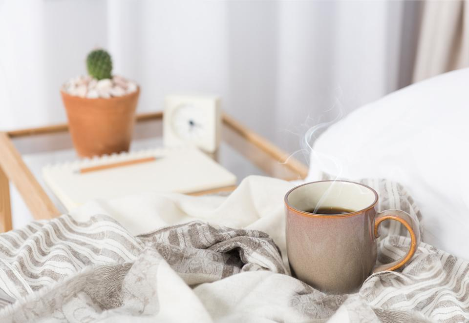 Cup of coffee on cozy white bed with cactus flowerpot,memo pat and alarm clock on wood bed side table