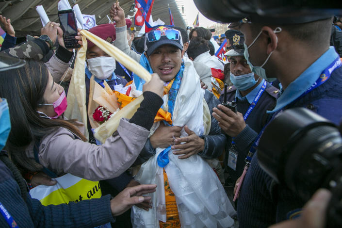 Nirmal Purja one of the team member of the all-Nepalese mountaineering team that became the first to scale Mount K2 in winter receives a scarf as they arrive at Tribhuwan International airport in Kathmandu, Nepal, Tuesday, Jan. 26, 2021. (AP Photo/Niranjan Shrestha)