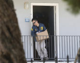 FILE - In this Aug. 15, 2018, file photo, an FBI agent removes items from an apartment following the arrest of Omar Ameen in Sacramento, Calif. A federal judge in California refused Wednesday, April 21, 2021, to allow the extradition to Iraq of Ameen, accused of killing for the Islamic State, saying cellphone evidence shows he was in Turkey at the time of the slaying. The U.S. Justice Department has tried since 2018 to return Omar Abdulsattar Ameen to Iraq under a treaty with that nation. (AP Photo/Rich Pedroncelli, File)