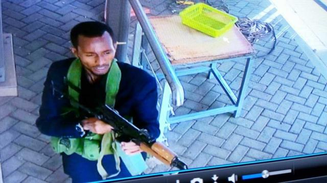 """In this grab taken from security camera footage released to the local media, an armed attacker walks in the compound of a hotel, in Nairobi, Kenya, Tuesday, Jan. 15, 2019. Extremists launched an attack on a luxury hotel in Kenya's capital, sending people fleeing in panic as explosions and heavy gunfire reverberate through the neighborhood. A police officer says he saw bodies, """"but there was no time to count the dead."""" Al-Shabab _ the Somalia-based extremist group _ is claiming responsibility. (Security Camera Footage via AP)"""