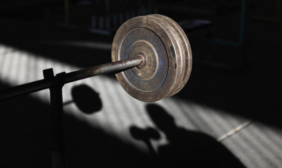 Weights are seen near the shadow of a man at a gym under the Alcantara Machado viaduct in the Mooca neighborhood of Sao Paulo July 18, 2012. Alcantara Machado gym was founded in 2009 by Brazilian former professional boxer Nilson Garrido under the Alcantara Machado viaduct, with the aim of getting young people out of drugs and crime through sports. Currently the gym, which received all its equipment through donations, is visited daily by more than a hundred people, most of whom are unemployed or have financial troubles, who practice bodybuilding and other sports just for pleasure.  Picture taken July 18, 2012. REUTERS/Nacho Doce (BRAZIL - Tags: SPORT SOCIETY OLYMPICS)