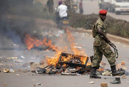 A Ugandan soldier stands in front of a burned barricade during clashes in Kampala