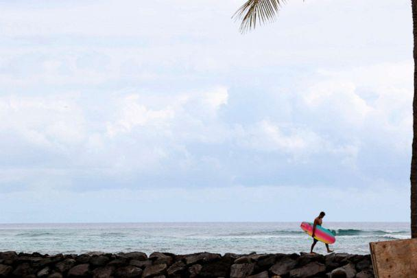PHOTO: A surfer returns to Waikiki Beach in Honolulu, April 21, 2020. Hawaii has some of the lowest coronavirus infection and mortality rates in the U.S. (Caleb Jones/AP)