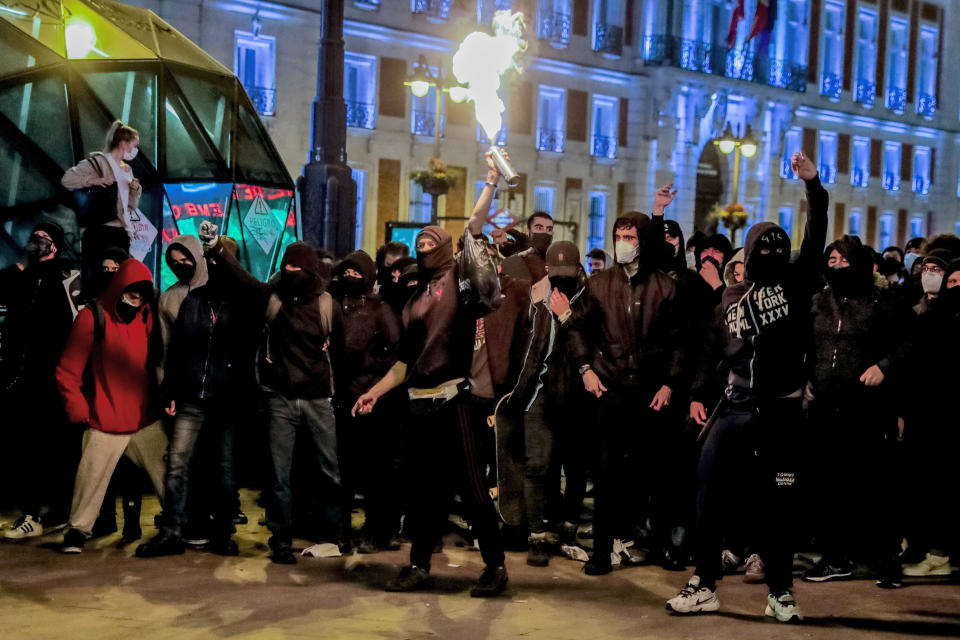 Demonstrators react during clashes as they protest against the arrest of rap artist Pablo Hasel in Madrid, Spain, Wednesday, Feb. 17, 2021. The imprisonment of a rap artist for his music praising terrorist violence and insulting the Spanish monarchy has set off a powder keg of pent-up rage this week in Spain. The arrest of Pablo Hasél has brought thousands to the streets for different reasons. The majority march under the banner of freedom of speech, but Hasél's lyrics also tap into a debate about the role of Spain's parliamentary monarchy after financial scandals involving the royal house. (AP Photo/Manu Fernandez)
