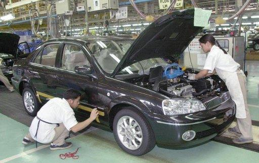 Workers assemble a car in the Ford plant near Manila