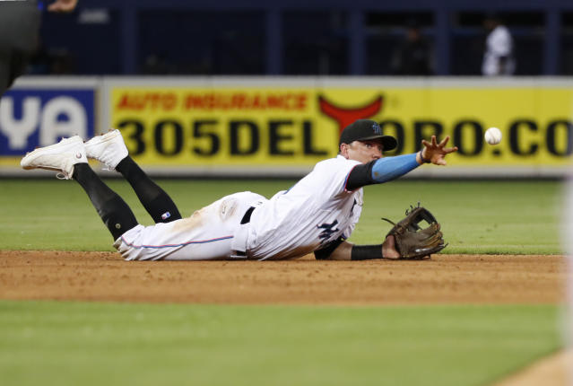 Miami Marlins shortstop Miguel Rojas tosses the ball to second baseman Starlin Castro to put out St. Louis Cardinals' Matt Carpenter at second for the first out of a double play hit into by Paul DeJong during the ninth inning of a baseball game, Wednesday, June 12, 2019, in Miami. The Marlins won 9-0. (AP Photo/Wilfredo Lee)