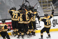 FILE - Teammates surround Boston Bruins right wing Craig Smith after his game-winning goal against the Washington Capitals during a second overtime period of Game 3 of an NHL hockey Stanley Cup first-round playoff series in Boston, in this Wednesday, May 19, 2021, file photo. The Bruins won 3-2. A pandemic postseason outside a bubble has led to some thrilling hockey after an exhausting, condensed 56-game grind. (AP Photo/Charles Krupa, FIle)