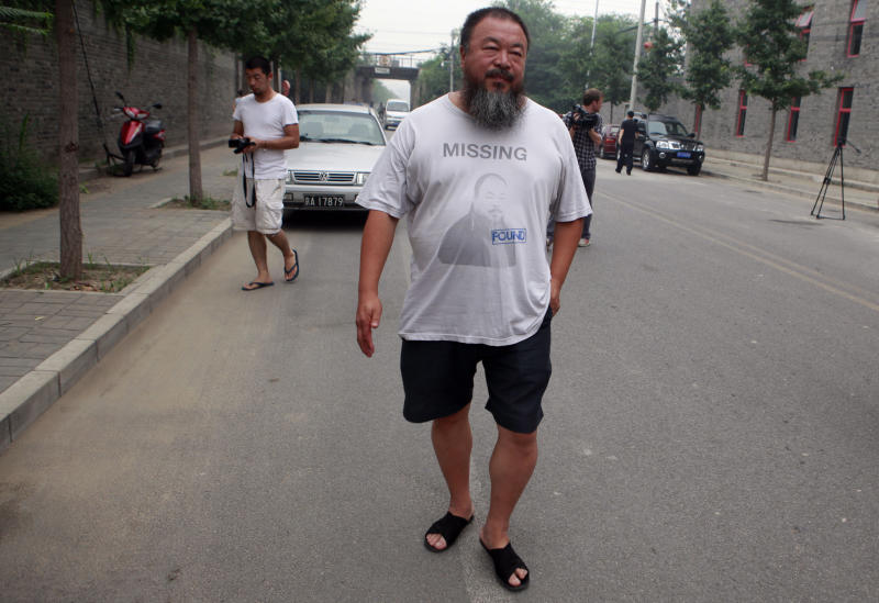 Dissident artist Ai Weiwei walks outside his home in Beijing, China, Friday, July 20, 2012. Chinese police on Friday barred Ai from attending the verdict on a lawsuit by his company against Beijing tax authorities. (AP Photo/Ng Han Guan)