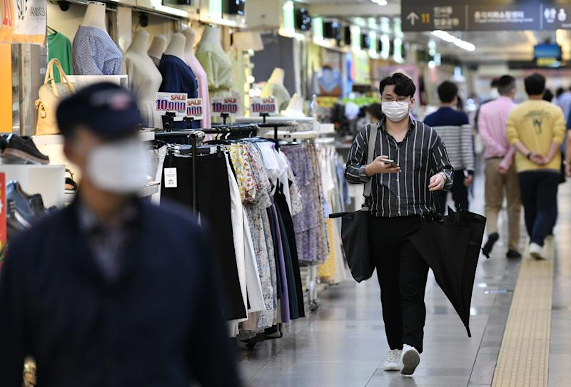 Pedestrians wearing face masks walk through an underground shopping area in central Seoul on June 2, 2020. - South Korea's economic contraction will worsen in the current quarter, the central bank forecast on June 2, as the COVID-19 coronavirus outbreak hits consumer demand and economic activity even harder. (Photo by Jung Yeon-je / AFP) (Photo by JUNG YEON-JE/AFP via Getty Images)